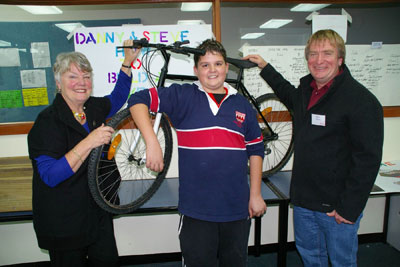 Heather Butler with Bridgewater High grade 7 student Danny Johns and volunteer mentor Steve Cooke, displaying the bicycle they had worked together to build from abandoned parts.