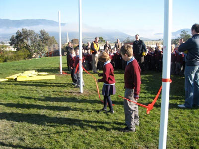 Students at St Paul's enjoy the 'cutting of the ribbon' of the newly refurbished oval's goal posts.