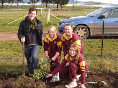 Anna Coventry who is with Brighton Council's engineering services with students Laura Millhouse, right,  Madilyn Walker,  front, and  Montanna Cate ensure their trees are firmly planted as part of national tree day.