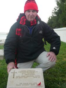 Mayor Tony Foster at the gravestone of the Anzac stretcher bearer John Simpson Kirkpatrick, better known as 'the man with the donkey'.